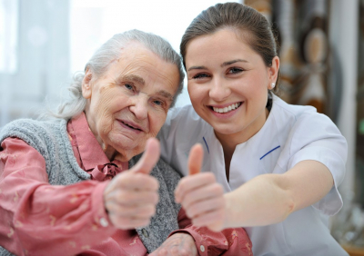 senior woman and her caregiver giving thumbs up