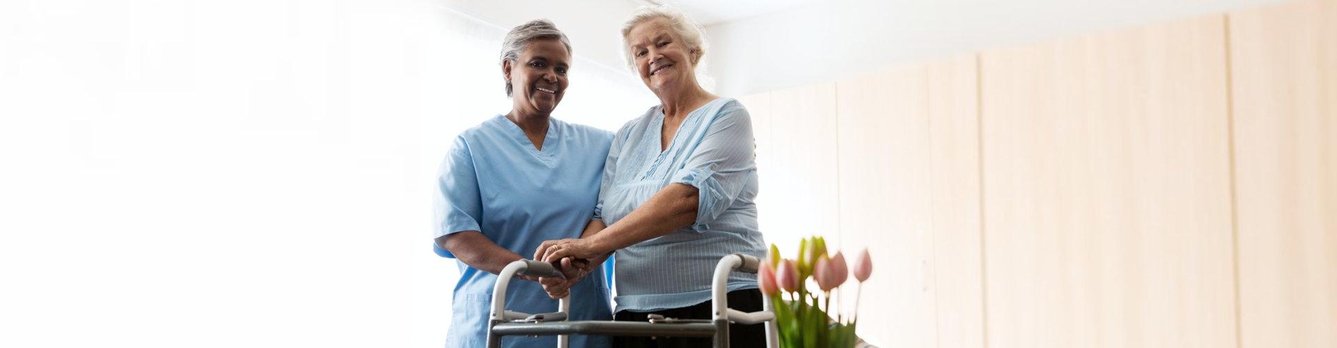 nurse standing by senior woman holding walker in nursing home